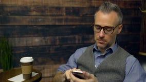 El hombre bebe el café en un café mientras que usa el teléfono almacen de video