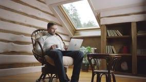 El hombre bebe el café por el ordenador portátil en el ático metrajes