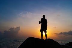 El hombre bebe de una botella en el amanecer Imagen de archivo libre de regalías