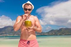 El hombre bebe el jugo de una nuez del coc en una playa Foto de archivo libre de regalías