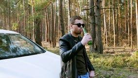 El hombre bebido bebe la cerveza cerca del coche y lanza hacia fuera una botella en naturaleza metrajes