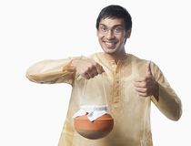 El hombre bengalí que lleva un pote de rasgulla y que muestra manosea con los dedos encima de sig Imagen de archivo