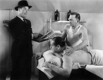 El hombre bien vestido que lee a un hombre que esté consiguiendo un masaje (todas las personas representadas no es un vivo más la fotografía de archivo libre de regalías