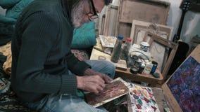 El hombre blanco-cabelludo pinta una imagen 4K disponible almacen de video