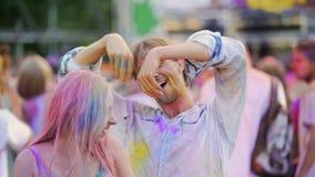 El hombre borracho cubierto en Holi colorea la ejecución de la danza loca, risa de la mujer joven almacen de video