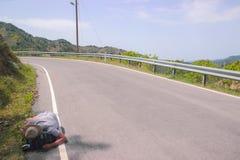 El hombre borracho duerme en la carretera imagenes de archivo