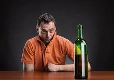 El hombre borracho mira la botella fotografía de archivo libre de regalías