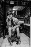 El hombre borracho se sienta en un retrete con el whisky imagen de archivo libre de regalías
