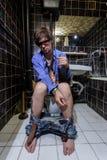 El hombre borracho se sienta en un retrete con una botella de whisky fotos de archivo