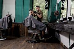 El hombre brutal con la barba del tha sienta en la silla en frente el espejo en una peluquería de caballeros Los afeitados del pe imágenes de archivo libres de regalías