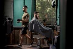 El hombre brutal con la barba se sienta en un chire en una peluquería de caballeros El peluquero hermoso pasa al lado de él fotos de archivo libres de regalías