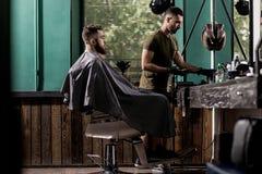 El hombre brutal con la barba se sienta en un chire en una peluquería de caballeros El peluquero hermoso toma el hairclipper foto de archivo libre de regalías