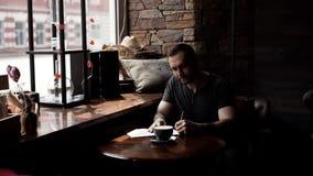 El hombre brutal que se sienta por la ventana con los brazos tatuados en caf? toma notas en coj?n metrajes