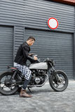 El hombre brutal se sienta en la moto de la aduana del corredor del café Fotografía de archivo libre de regalías