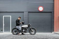 El hombre brutal se sienta en la moto de la aduana del corredor del café Foto de archivo