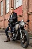 El hombre brutal se sienta en la moto de la aduana del corredor del café Fotos de archivo