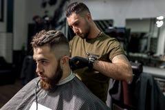 El hombre brutal se sienta en la silla en una peluquería de caballeros El peluquero en guantes negros afeita los pelos del hombre fotos de archivo libres de regalías