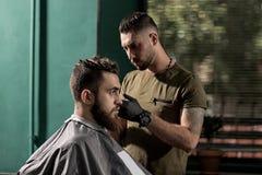 El hombre brutal se sienta en una peluquería de caballeros El peluquero hace un ajuste imágenes de archivo libres de regalías