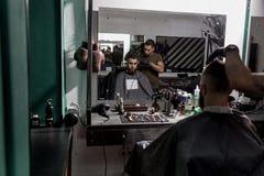 El hombre brutal sienta en la silla en una peluquería de caballeros en frente el espejo Los afeitados del peluquero sirven los pe fotografía de archivo libre de regalías