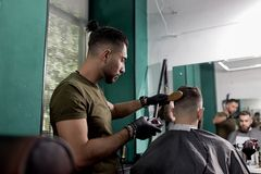 El hombre brutal sienta en una peluquería de caballeros en frente el espejo El peluquero en guantes negros afeita los pelos del h foto de archivo