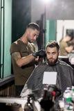 El hombre brutal sienta en una peluquería de caballeros en frente el espejo El peluquero hace un ajuste del pelo foto de archivo libre de regalías