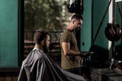El hombre brutal sienta en una peluquería de caballeros en frente el espejo El peluquero toma el hairclipper imagen de archivo libre de regalías