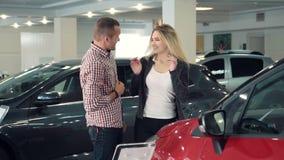 El hombre a cámara lenta sorprende la esposa o a la novia en la concesión de coche, mostrando el nuevo coche metrajes
