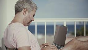 El hombre cabelludo gris hermoso trabaja en su ordenador portátil en terraza de la opinión del mar en sol brillante almacen de metraje de vídeo