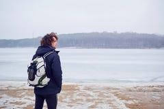 El hombre cabelludo rizado en una chaqueta con invierno de la mochila en el lago viaja Foto de archivo