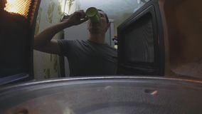 El hombre calienta el café en la opinión de primera persona a del horno de la forma de vida de la microonda dentro almacen de video