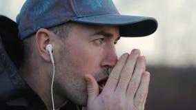 El hombre calienta las manos al aire libre almacen de video
