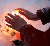 El hombre calienta las manos congeladas en el invierno por un fuego minúsculo foto de archivo libre de regalías