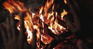 El hombre calienta sus manos delante de un fuego abierto El concepto que acampa con al aire libre abre las llamas del fuego Turis metrajes