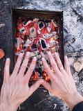 El hombre calienta sus manos delante de un fuego abierto El concepto que acampa con al aire libre abre las llamas del fuego Turis fotografía de archivo