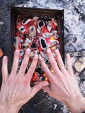 El hombre calienta sus manos delante de un fuego abierto El concepto que acampa con al aire libre abre las llamas del fuego Turis imagen de archivo libre de regalías