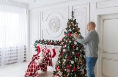 El hombre calvo adorna un árbol de navidad Imagenes de archivo