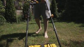El hombre calvo gordo con las tetas al aire siega descalzo el cortac?sped amarillo del c?sped almacen de video