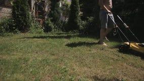 El hombre calvo gordo con las tetas al aire siega descalzo el cortac?sped amarillo del c?sped metrajes