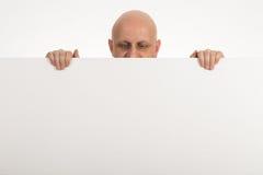 El hombre calvo mira furtivamente sobre el top de Libro Blanco en blanco fotos de archivo libres de regalías