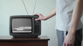 El hombre cambia los canales en la TV vieja almacen de video