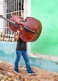 El hombre camina abajo de la calle que lleva su violoncelo en su hombro Fotos de archivo libres de regalías