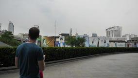 El hombre camina abajo de la calle y de las fotografías en el smartphone Sirva la fabricación de la foto con su móvil en la calle almacen de metraje de vídeo