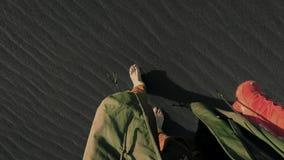 El hombre camina barefeet en la playa negra de la arena almacen de metraje de vídeo