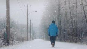 El hombre camina en el camino en la nieve almacen de metraje de vídeo