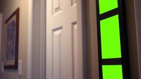 El hombre camina en cuarto de baño con las imágenes verdes de la pantalla en primero plano almacen de metraje de vídeo