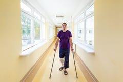 El hombre camina en las muletas Foto de archivo