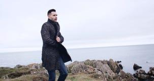 El hombre camina en marco y los soportes, mirando hacia fuera sobre el océano extenso y el cielo nublado en Irlanda, modelan lanz metrajes