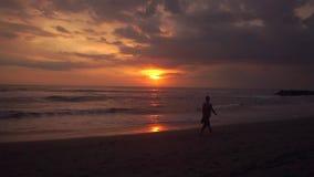 El hombre camina la playa en la puesta del sol