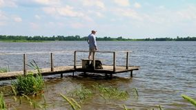 El hombre camina y se coloca en el embarcadero en el lago en tiempo ventoso almacen de metraje de vídeo