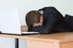 El hombre cansado de la oficina toma resto en Front His Computer Foto de archivo